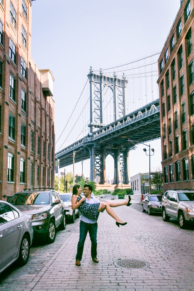 Man carrying woman in front of Manhattan Bridge