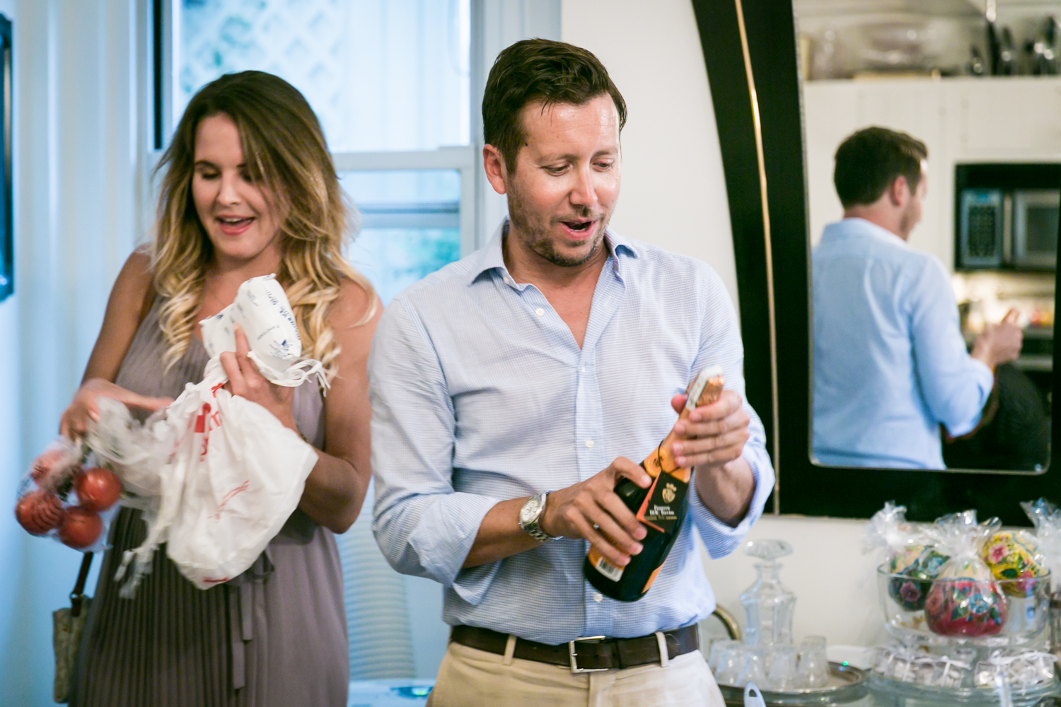 Man opening bottle of champagne at a NYC rehearsal dinner in a Manhattan apartment