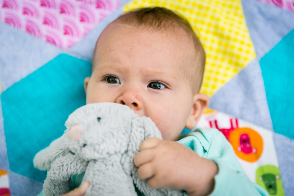 Baby chewing stuffed rabbit on quilt