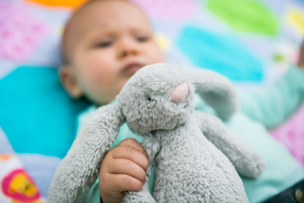 Baby holding stuffed rabbit on quilt by Brooklyn baby photographer, Kelly Williams