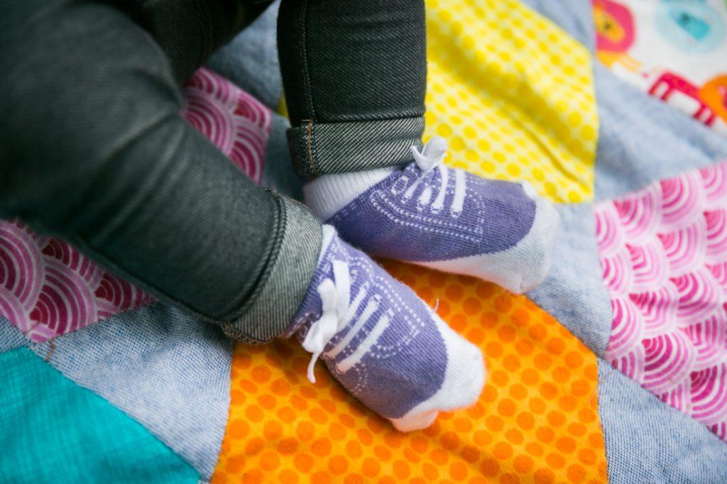 Close up of baby feet wearing sneaker socks