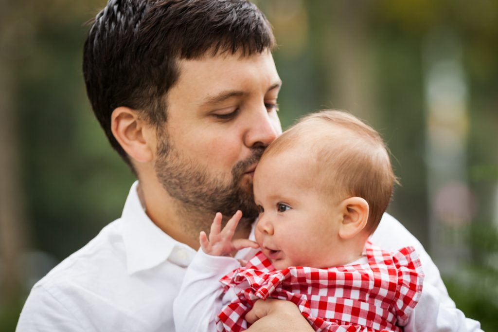 Father kissing little girl's head
