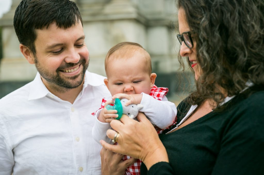 Parents holding little girl chewing on toy
