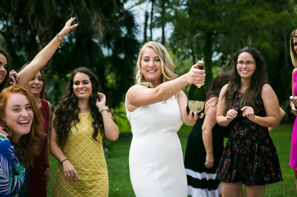 Bride-to-be opening a bottle of champagne with guests at a Florida bridal shower