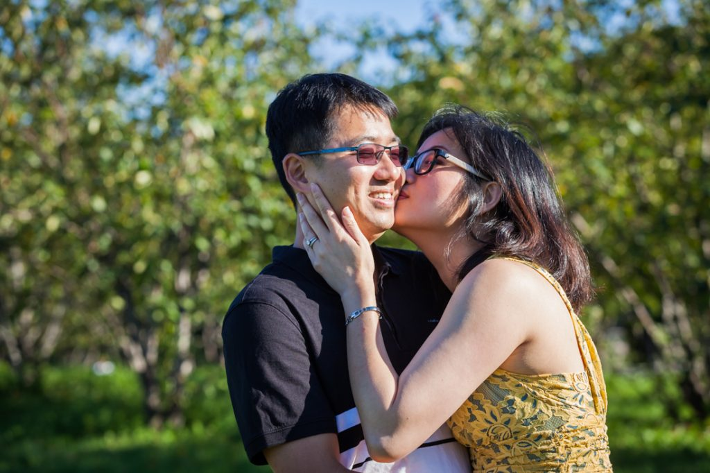 Woman kissing husband by Kew Gardens family photographer, Kelly Williams