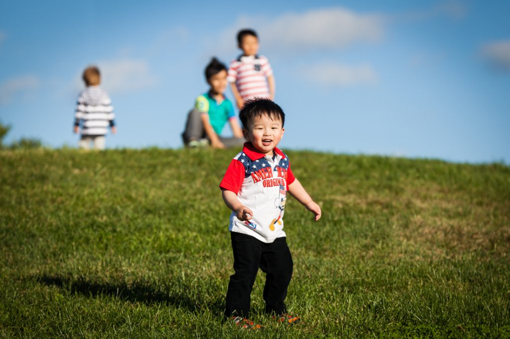 Little boy on grassy hill by Kew Gardens family photographer, Kelly Williams