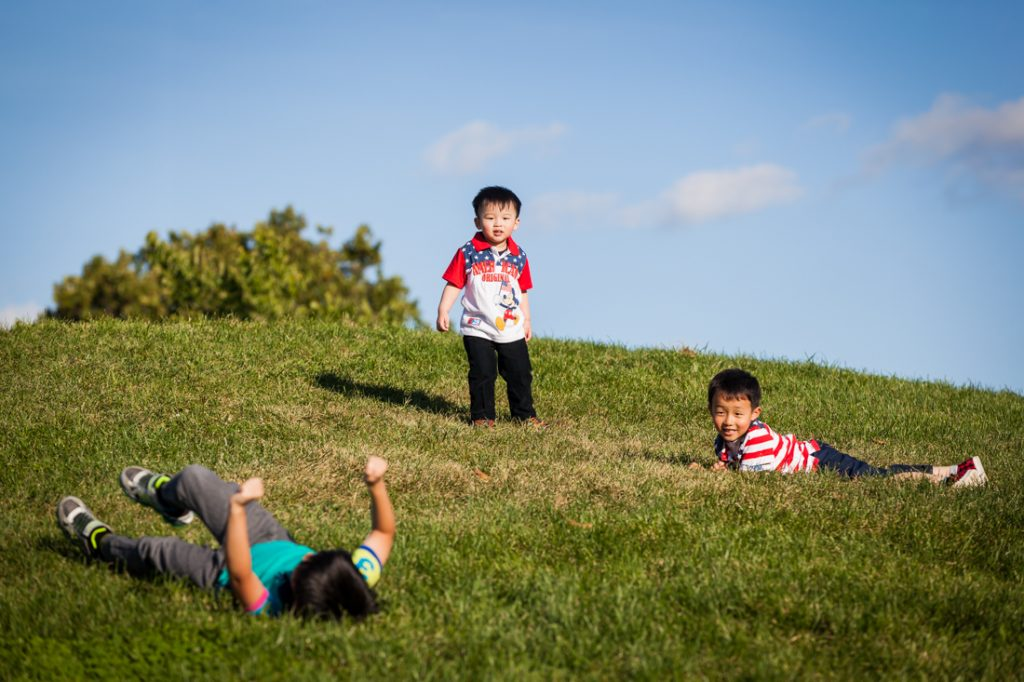 Three boys rolling down a grassy hill by Kew Gardens family photographer, Kelly Williams
