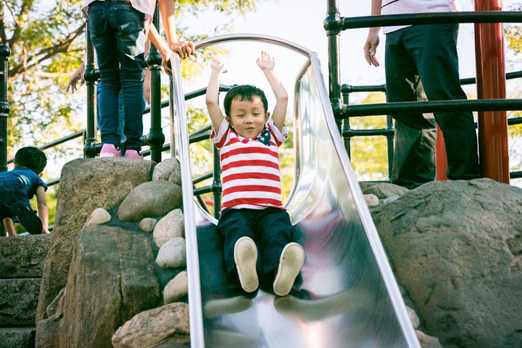Boy going down slide in Elmhurst Park