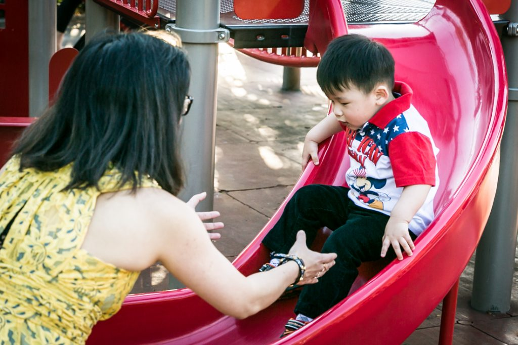 Mother catching little boy on slide in Elmhurst Park