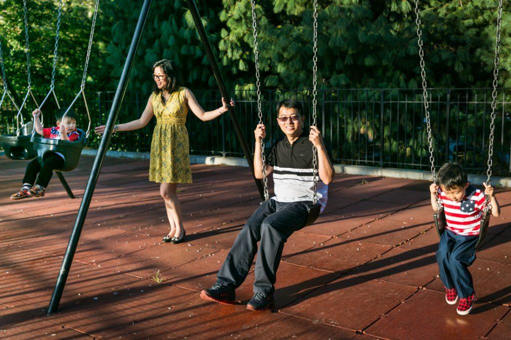 Parents on swing set in Elmhurst Park