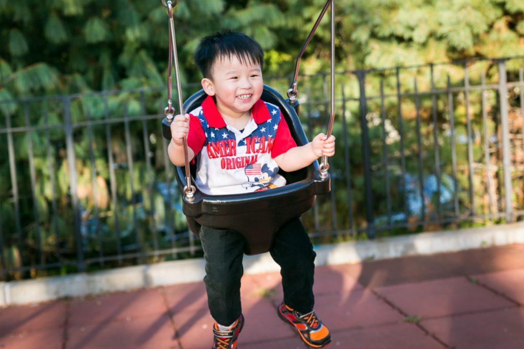 Little boy in swing in Elmhurst Park
