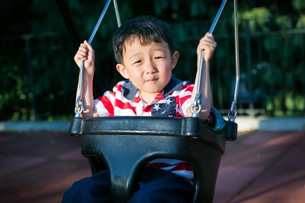 Little boy in swing at Elmhurst Park