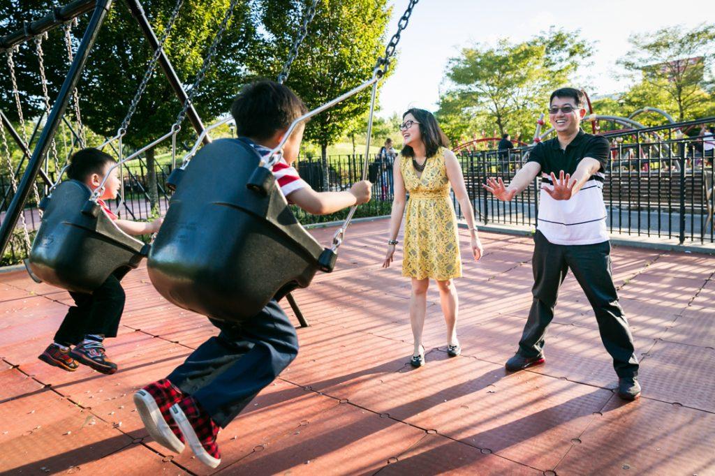 Parents pushing kids in swings at Elmhurst Park