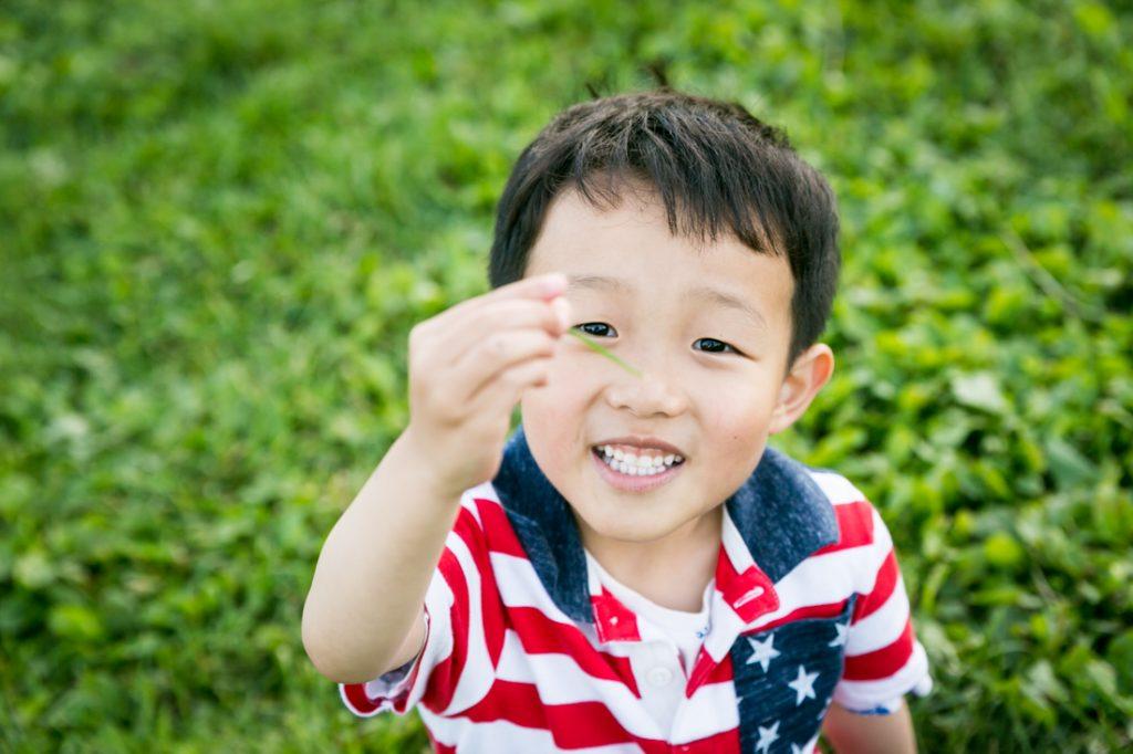 Boy holding up a blade of grass