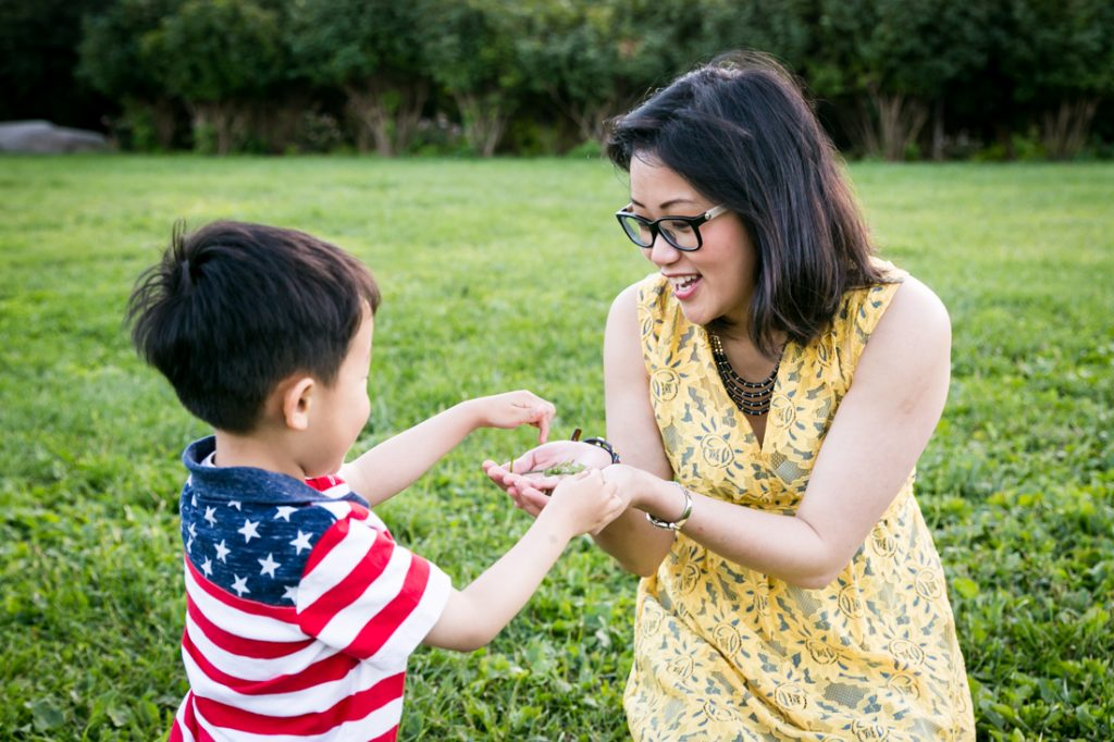 Boy giving grass to mother in Elmhurst Park
