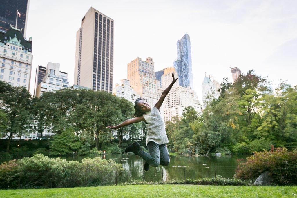 Central Park fall family portrait of girl jumping with NYC skyline in background