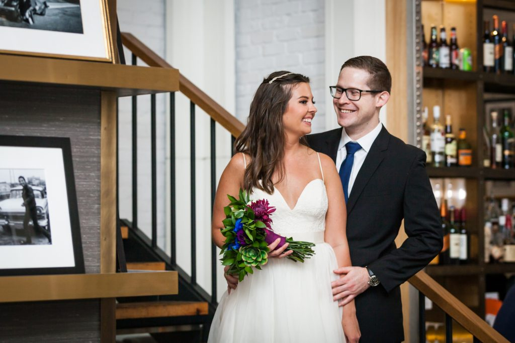 Portrait of bride and groom on hotel staircase for an article on how to book hotel room blocks