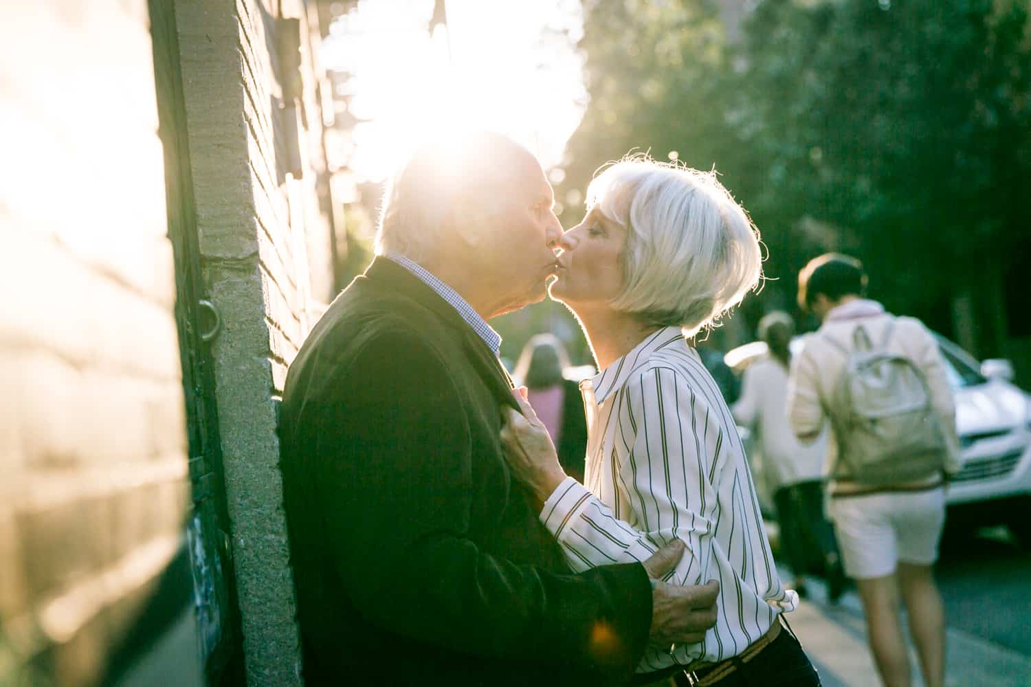 Photojournalistic portraits of older couple kissing against building