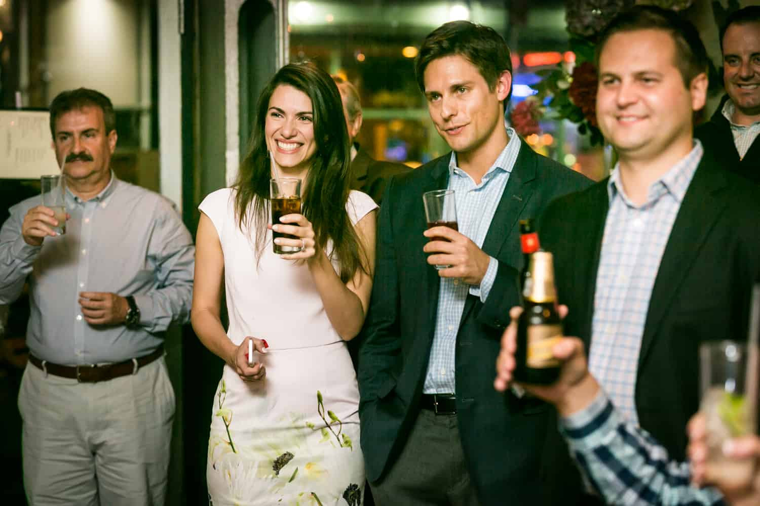 Couple and guests holding drinks for an article on rehearsal dinner tips