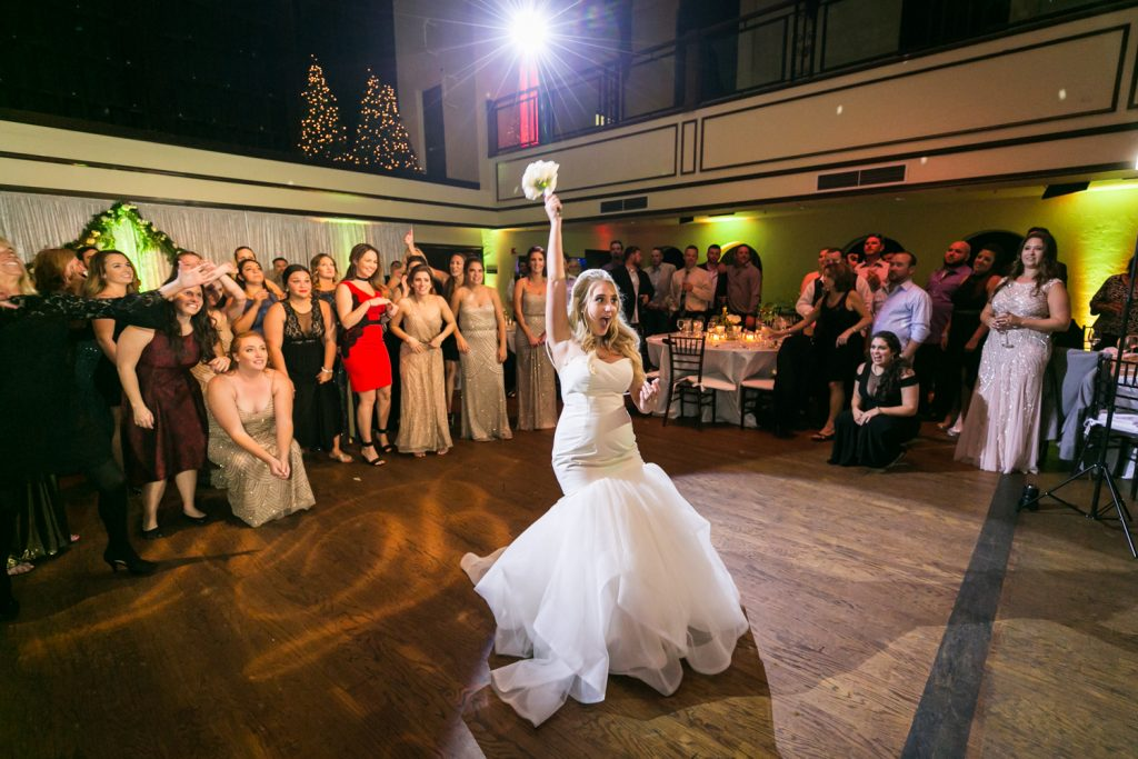 Bride with arm up about to throw bouquet at group of women for an article on how DJ lighting affects your wedding photos