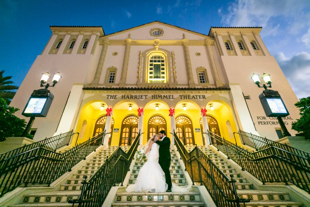 Bride and groom kissing on stairs of entrance to Harriet Himmel Theater for an article on how to have an unplugged wedding