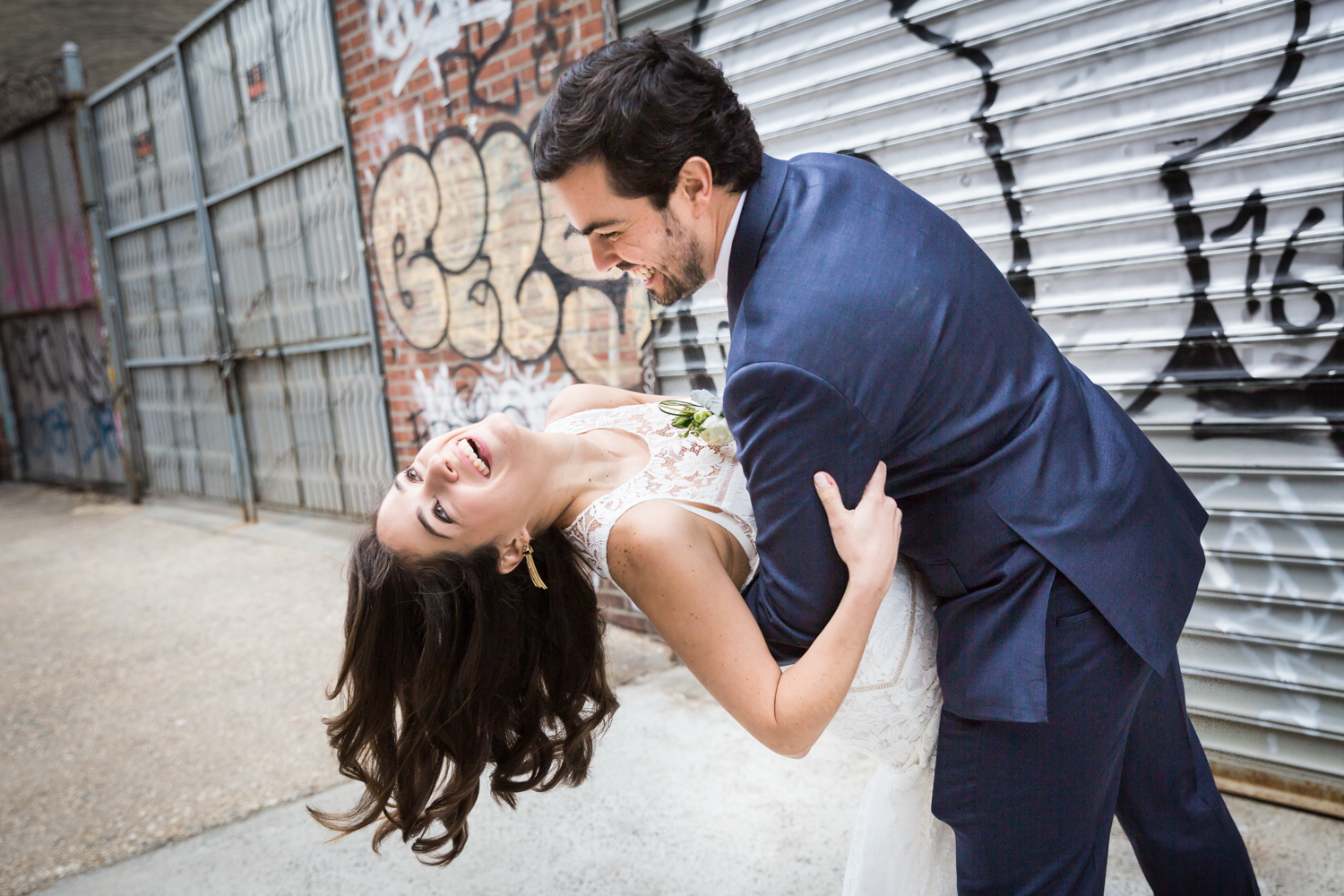 Groom dipping bride with graffiti background before a Wythe Hotel wedding