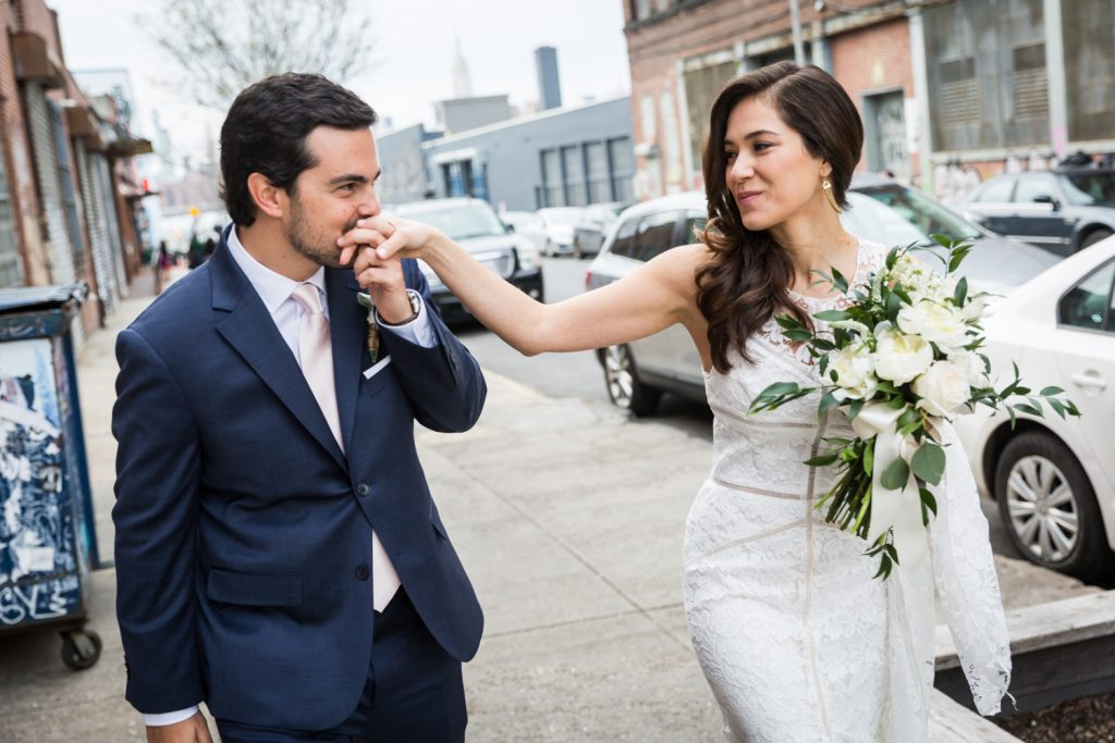 Groom kissing bride's hand on Brooklyn sidewalk