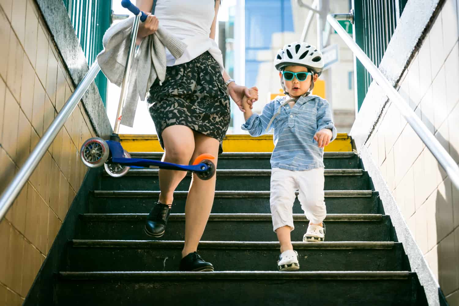 Little boy wearing sunglasses and helmet walking down stairs during a day in the life photography session