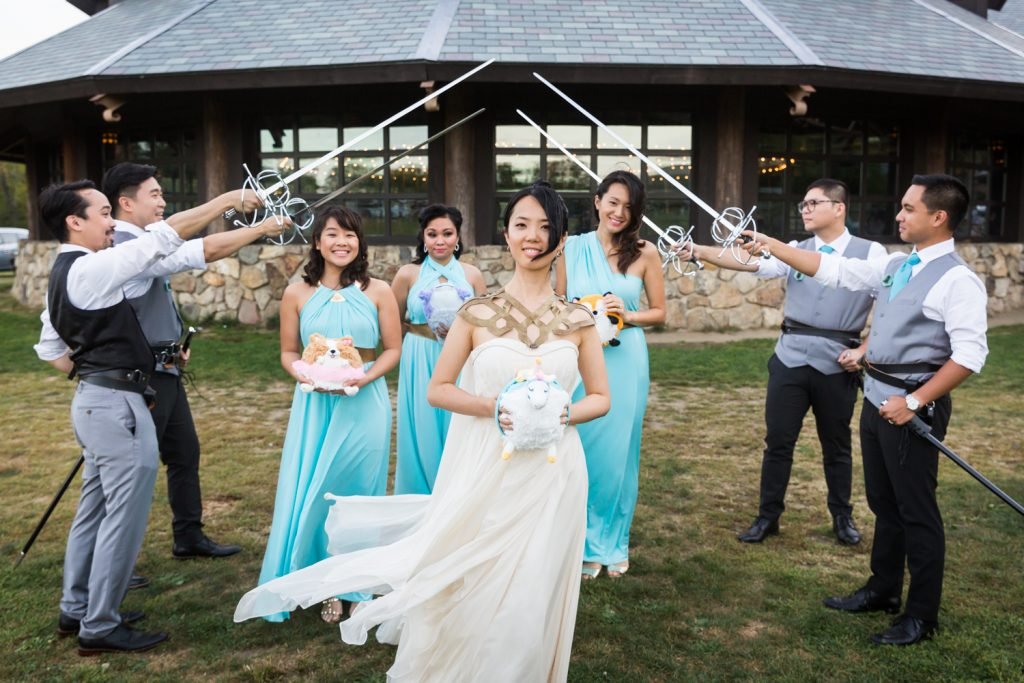 Groomsmen holding swords over the heads of bride and bridesmaids at a Bear Mountain Inn wedding