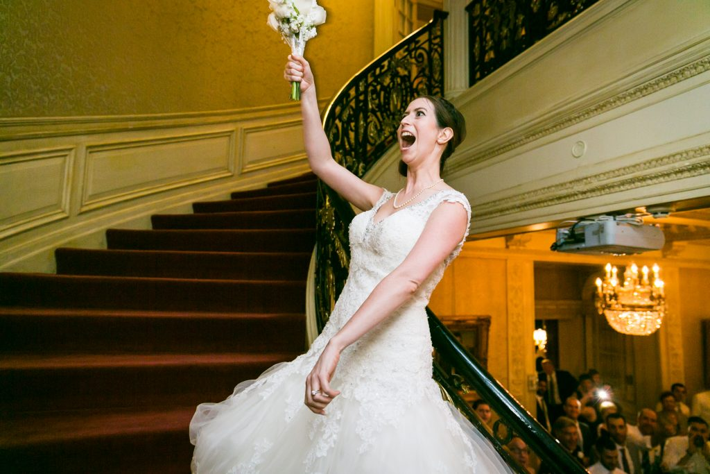 Bride tossing bouquet for an article on bouquet and garter toss alternatives