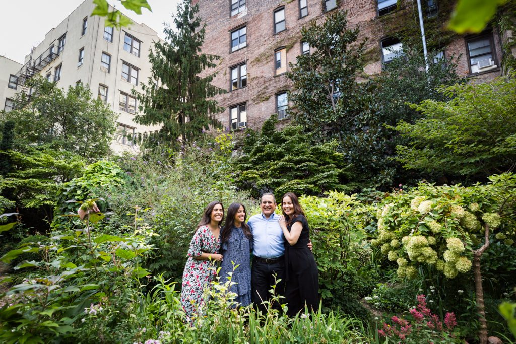 Family in middle of garden with apartment building in background at a community garden family portrait session