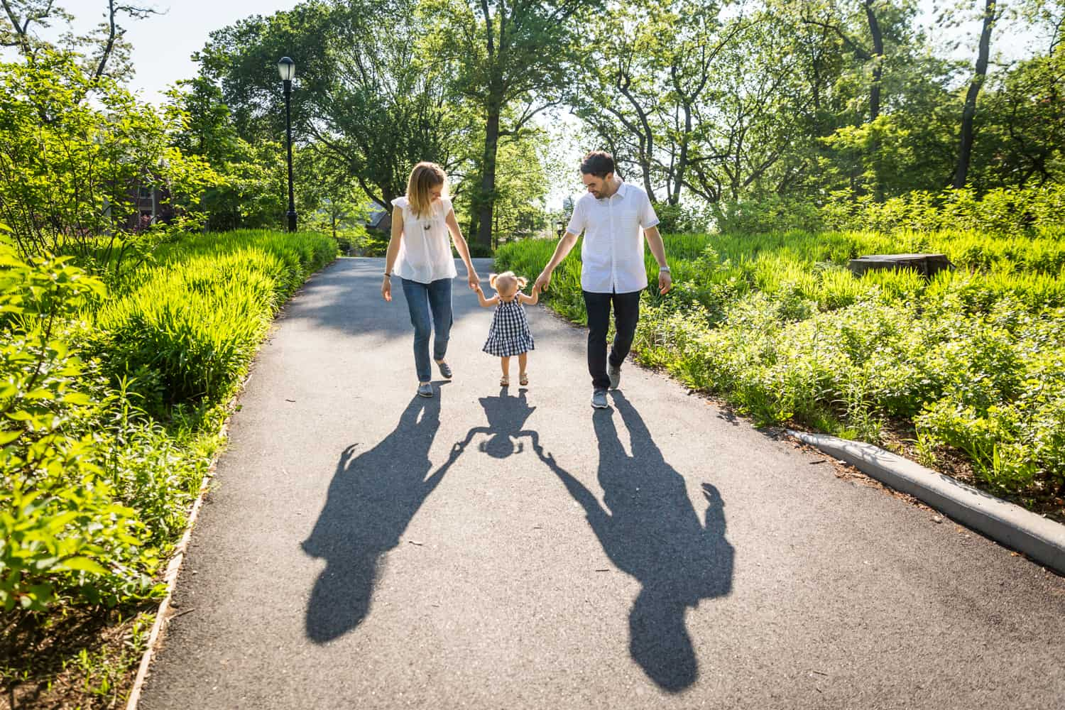 Parents holding hands with little girl in Forest Park for an article on toddler portrait tips