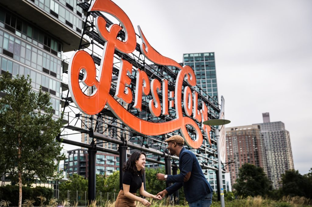Couple holding hands in front of neon Pepsi Cola sign for an article on Gantry Plaza State Park engagement portrait tips