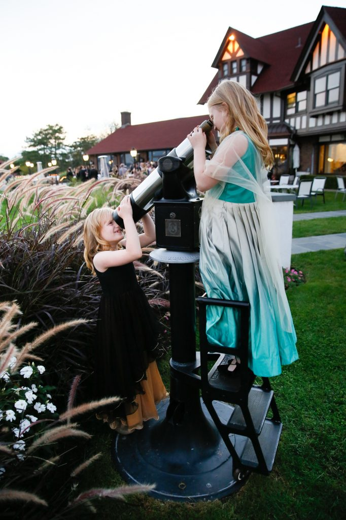 Two kids playing with telescope at a Larchmont Shore Club wedding