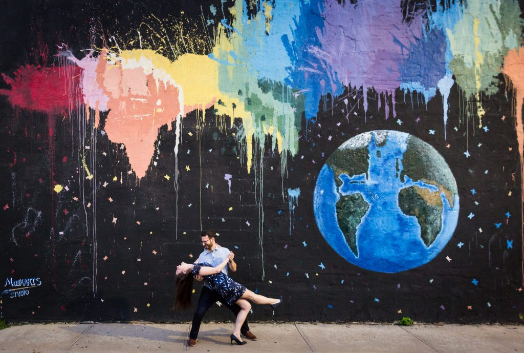 Couple dancing in front of colorful mural before their ketubah signing
