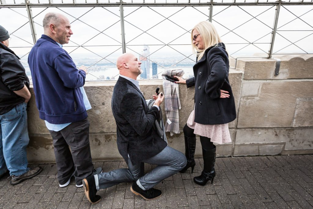 Man on one knee proposing to woman for an article on how to propose on top of the Empire State Building