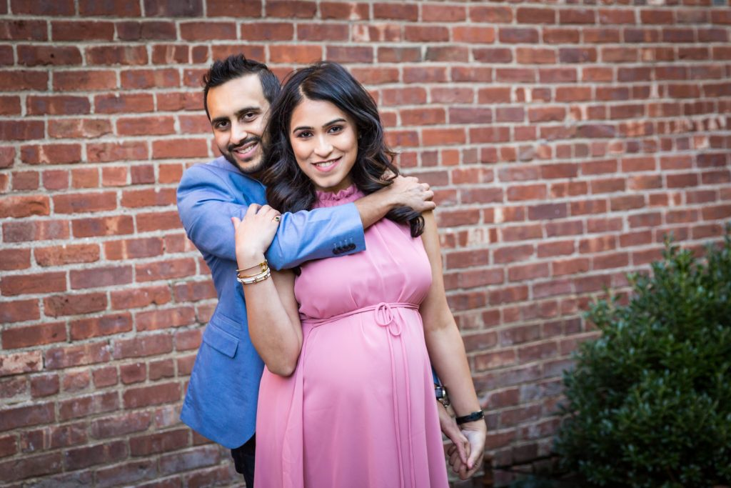 Portrait of pregnant woman and her husband with his arm around her shoulders for article on maternity portrait tips