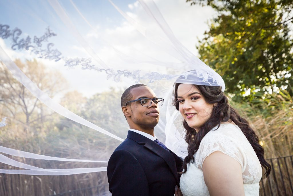 Portrait of groom and bride under blowing veil for an article on wedding photography timeline tips