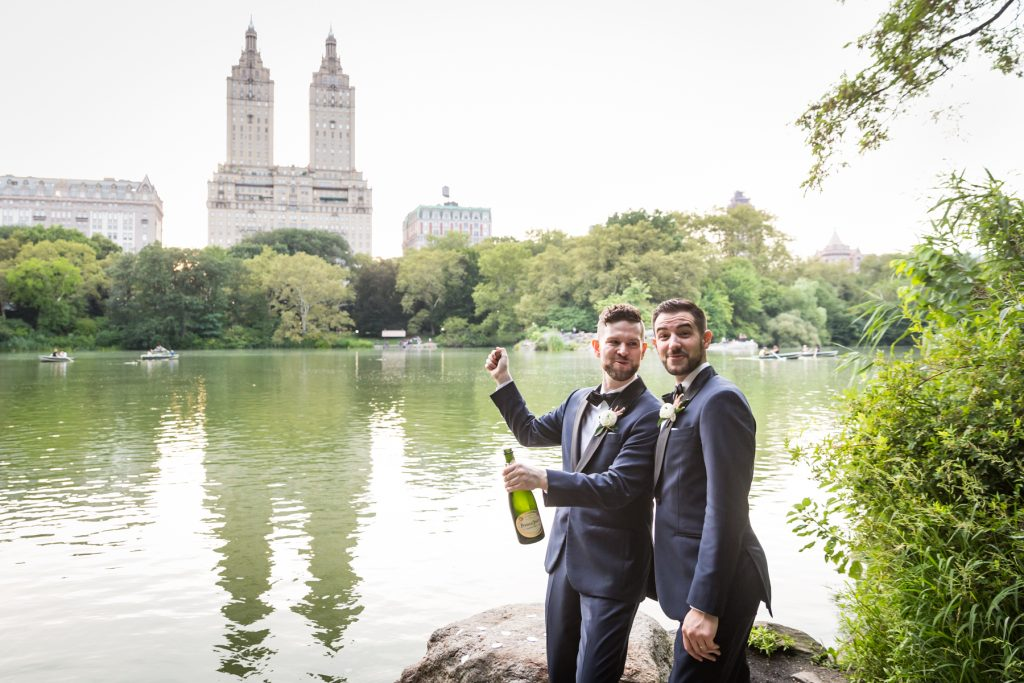 Two grooms popping open a bottle of champagne for an article entitled, 'Do you need a permit to get married in Central Park?'