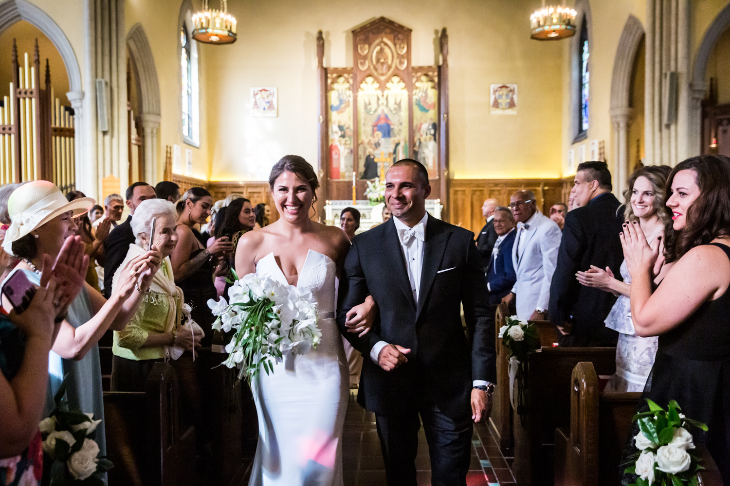 Bride and groom leaving Fordham University Church for an article on Bronx Zoo wedding venue updates