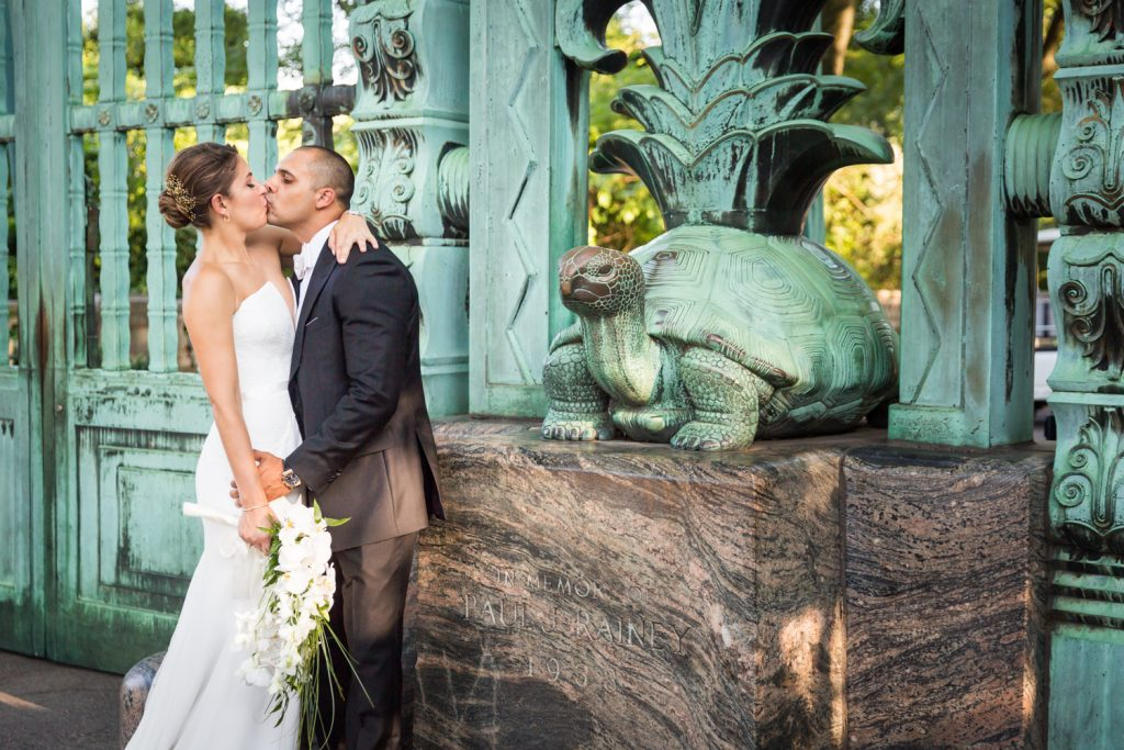 Bride and groom kissing by Southern Boulevard gate turtle for an article on Bronx Zoo wedding venue updates