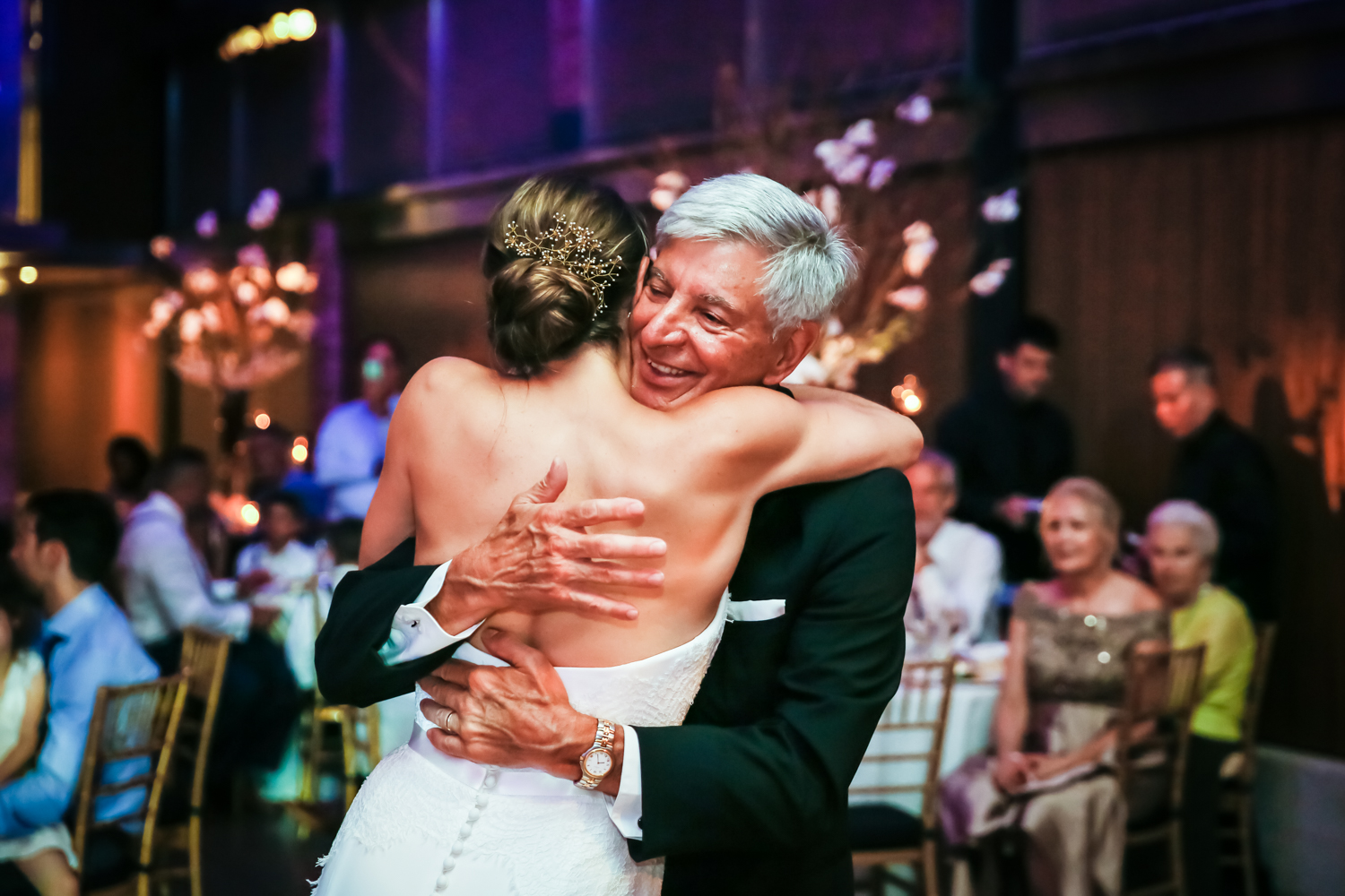 Bride and father hugging for an article on Bronx Zoo wedding venue updates