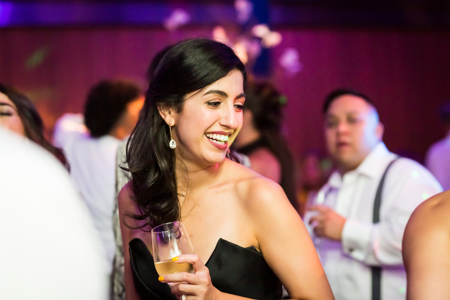 Guest with champagne glass dancing for an article on Bronx Zoo wedding venue updates