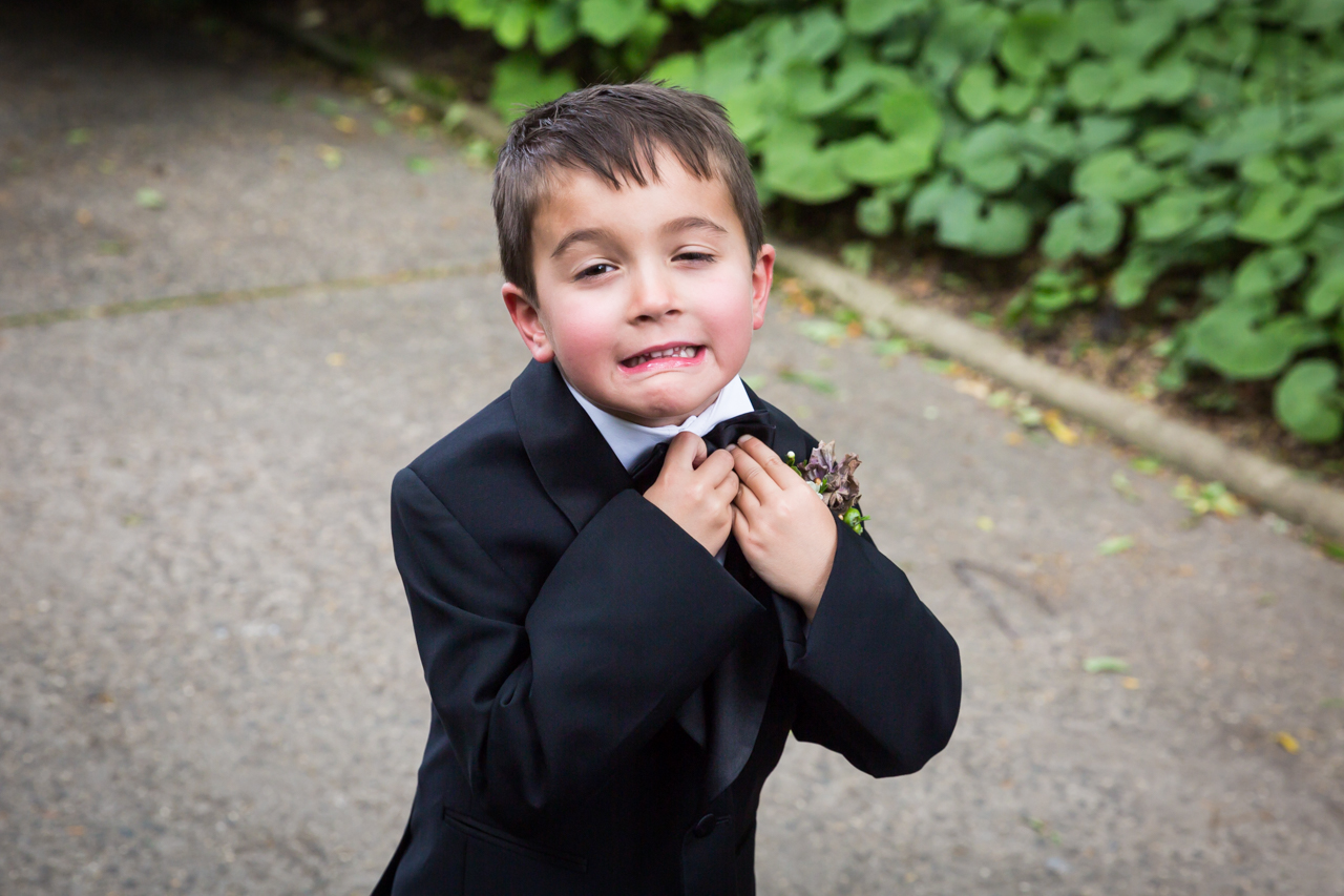 Ring bearer adjusting tie at a Central Park Conservatory Garden wedding