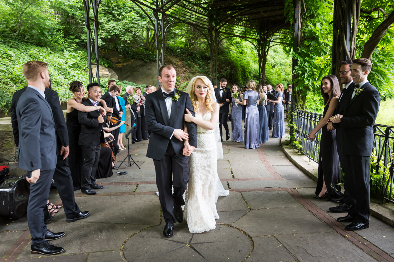 Bride and groom walking aisle after ceremony at a Central Park Conservatory Garden wedding
