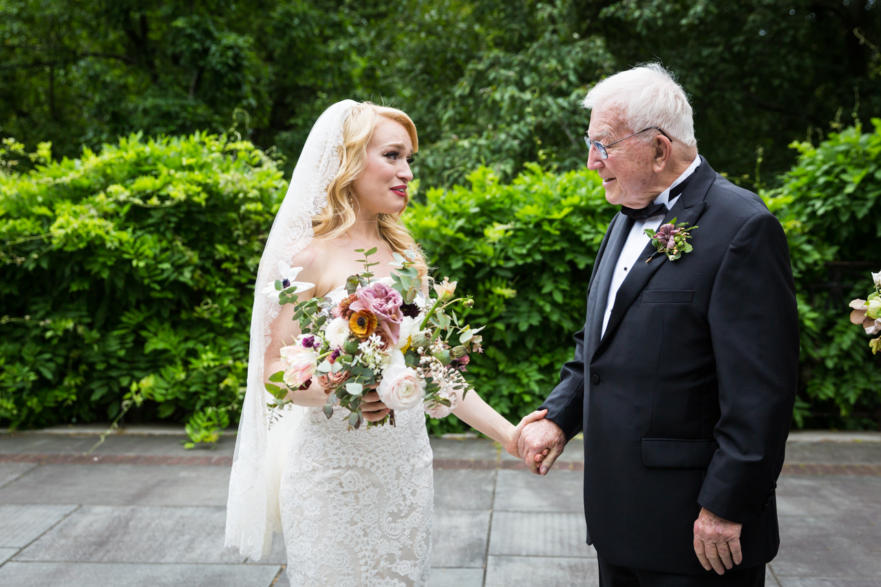 Bride and grandfather holding hands at a Central Park Conservatory Garden wedding
