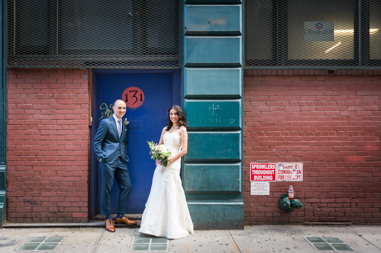 Bride and groom in colorful doorway for an article on non-floral centerpiece ideas