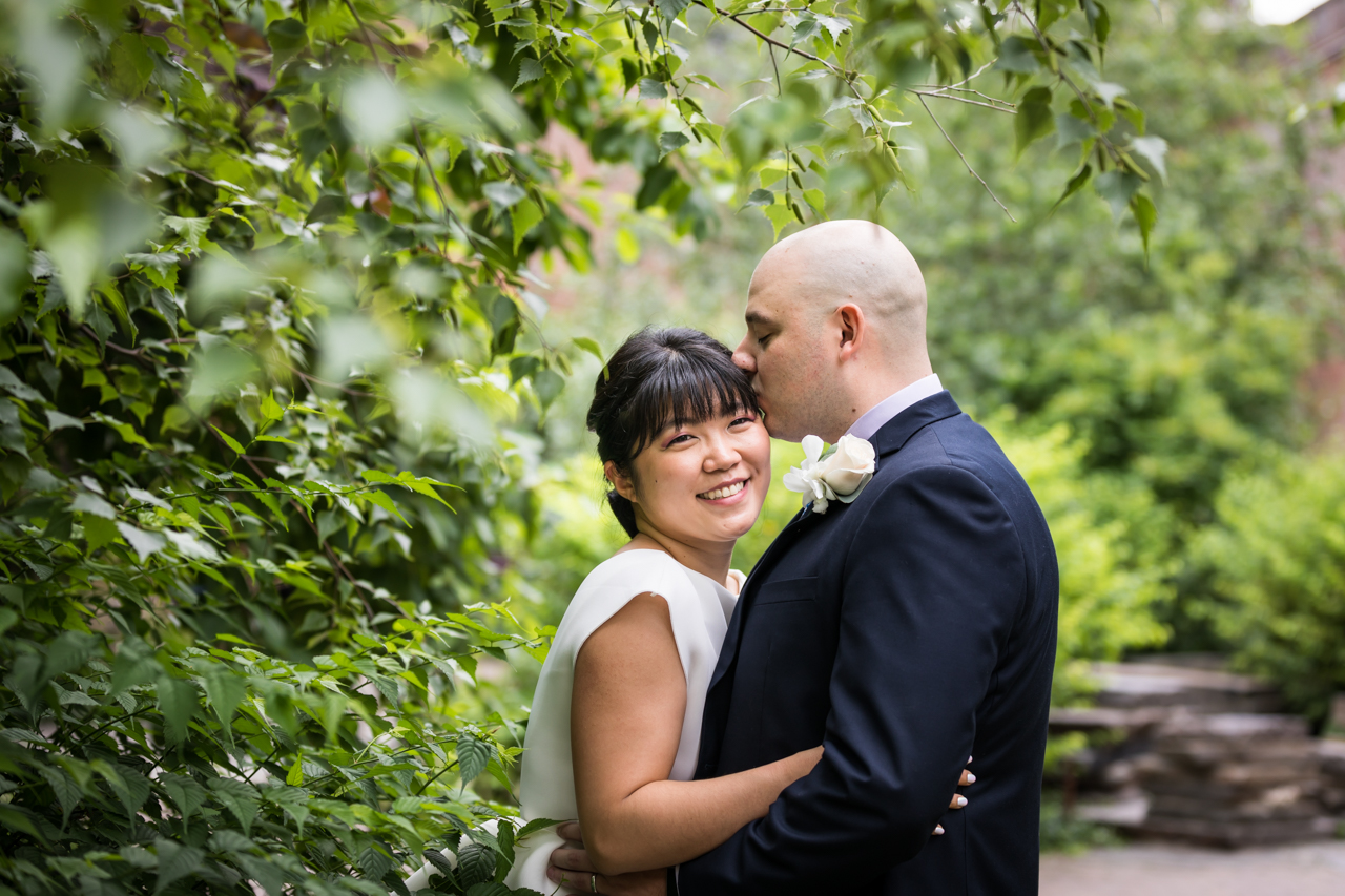 Man kissing woman on forehead in Brooklyn Bridge Park