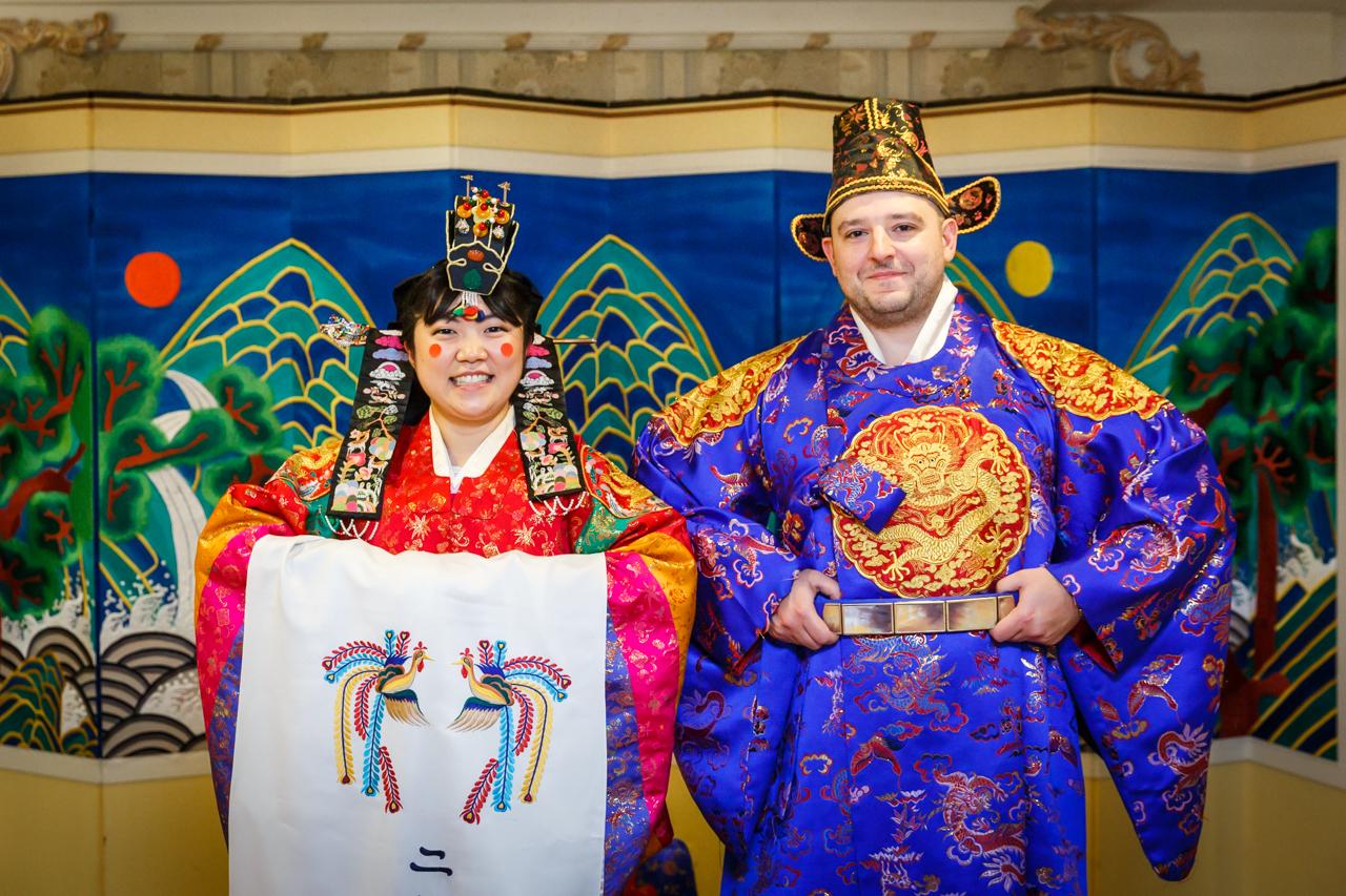 Formal portrait of bride and groom wearing hanbok at traditional Korean pyebaek ceremony