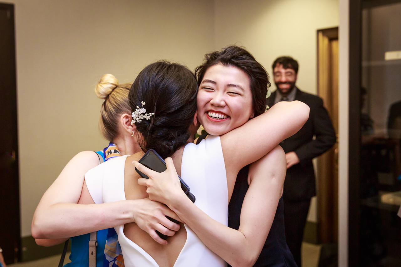 Bride and sister hugging after NYC City Hall wedding